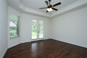 MASTER BEDROOM - tray ceiling, ceiling fan, vinyl plank flooring, french doors to covered patio