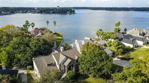 Aerial view of the front of the home with Lake Conroe in the background. Note roof is only a few years old. Home is located on a short cove, but is very close to open water and has views looking across Lake Conroe.