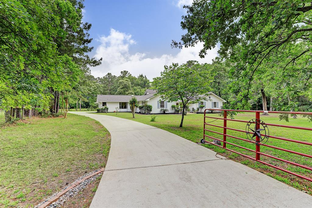 One-of-a-kind property with beautiful 1-story home boasts new roof, gutters, dishwasher & 5-yr old HVAC and is nestled on a fully fenced, wooded 4.67-acre tract that offers the best of both worlds-a rural setting permitting horses, yet just minutes from suburban amenities!  Property offers fig, pear, pecan, apple & pomegranate trees, 1-acre fenced pasture, 2-stall horse barn plumbed for water & chicken coop. Seasonal wet-weather Deer Creek runs through back of land & designed by Corp of Engineers to dump into Lake Hardin & property has water detention ditch. Home has hardwood, travertine & porcelain tile floors. With spacious, updated kitchen, large living areas, sizable bedrooms, amazing master bath w-double shower & huge laundry room, this fine home has it all! Charming flagstone front patio & covered back porch w-extended deck are ideal for enjoying the scenic outdoors. Water to home provided by public water system. 2 septic systems on property. Home has never flooded! Low taxes.