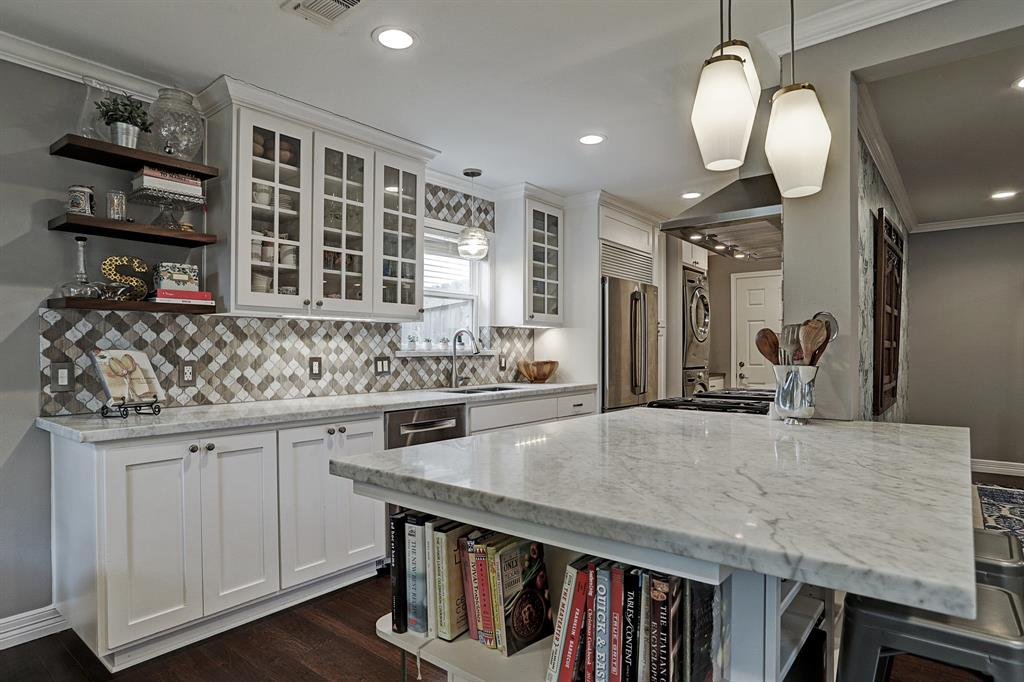 Recessed lighting illuminates the wonderful kitchen. Kitchen countertop features a ledge perfect for two barstools.