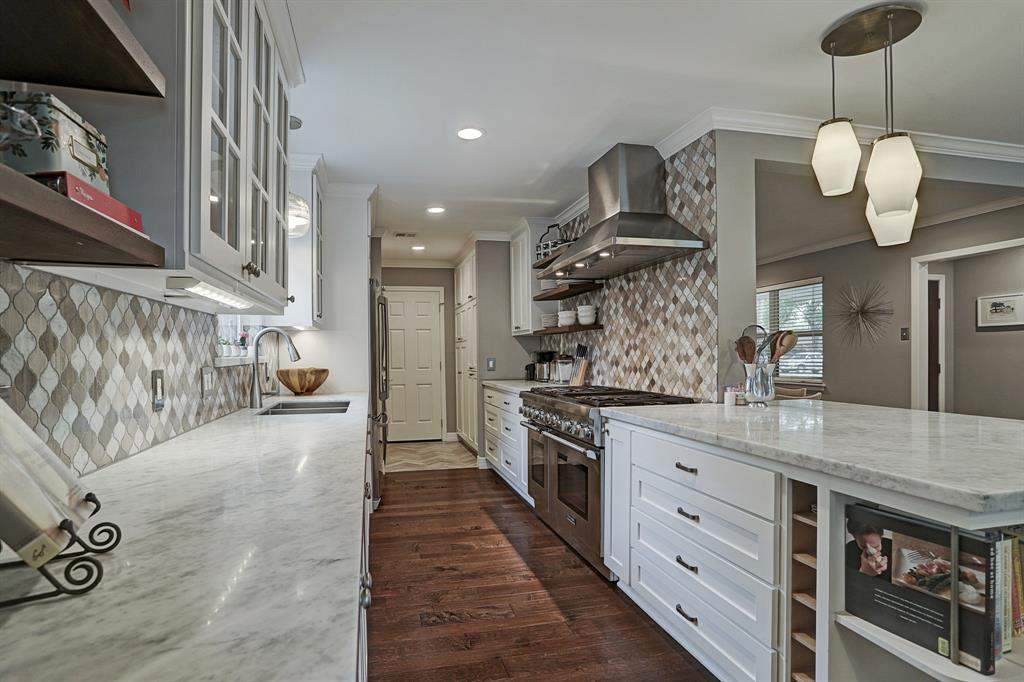 Light marble countertops, modern backsplash, Thermador Range and hood, glass and open shelving, and custom designed cabinets are all great storage.