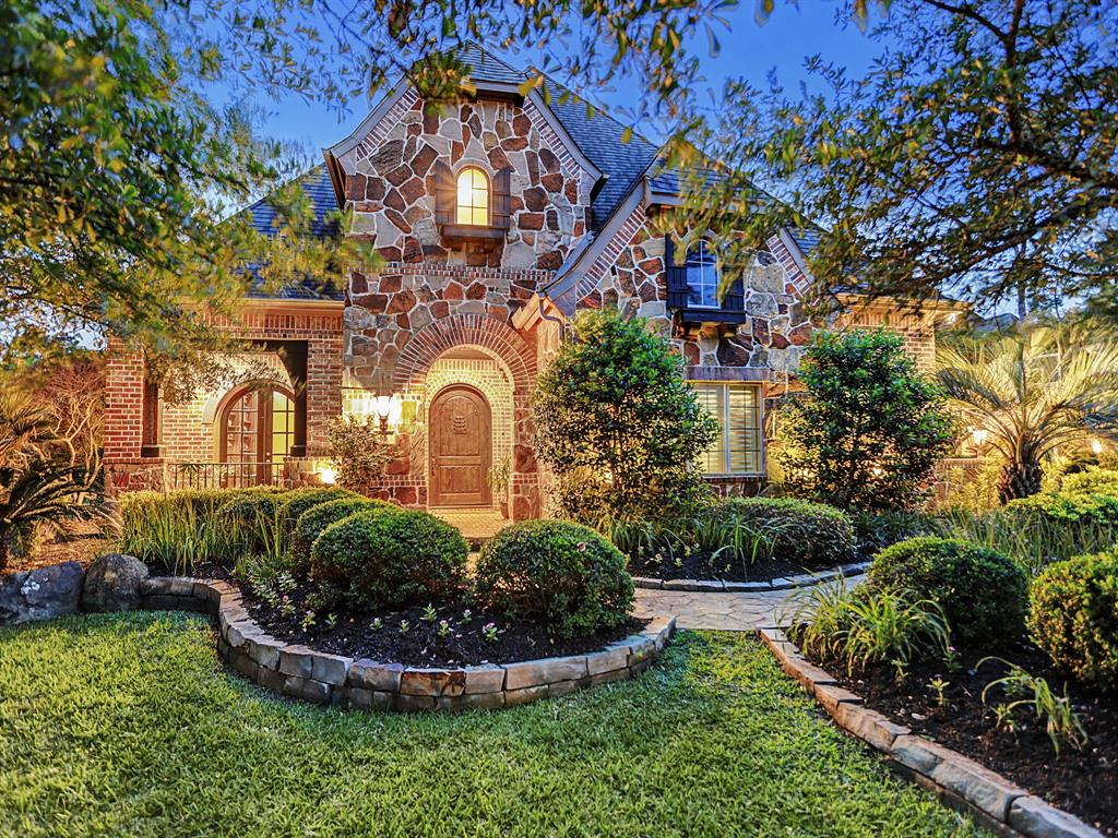 This modern day brick and stone Tudor manor house presents as if it belongs in the English countryside. Architectural details such as extensive masonry work, covered brick veranda, and oversized custom front door enchant. This one of a kind floor plan will not be found elsewhere in The Woodlands! Attributes such as tongue and groove ceilings, hand-scraped hardwoods, impressive millwork and built-ins are throughout the home. The spacious gourmet kitchen, the family room's cathedral ceiling and walls of windows allow for effortless living and entertaining. Two Bedroom suites on the main level! Perched atop a sprawling lot, the property enjoys an oversized beach entry pool with flowing waterfalls, fountain and spa. Repeating brick archways reveal an extensive covered outdoor living area with fireplace and summer kitchen, complete with grill, sink and refrigerator. Dedicated pool bath! Live your fairy tale in this stately but charming present day Tudor. Outstanding schools.