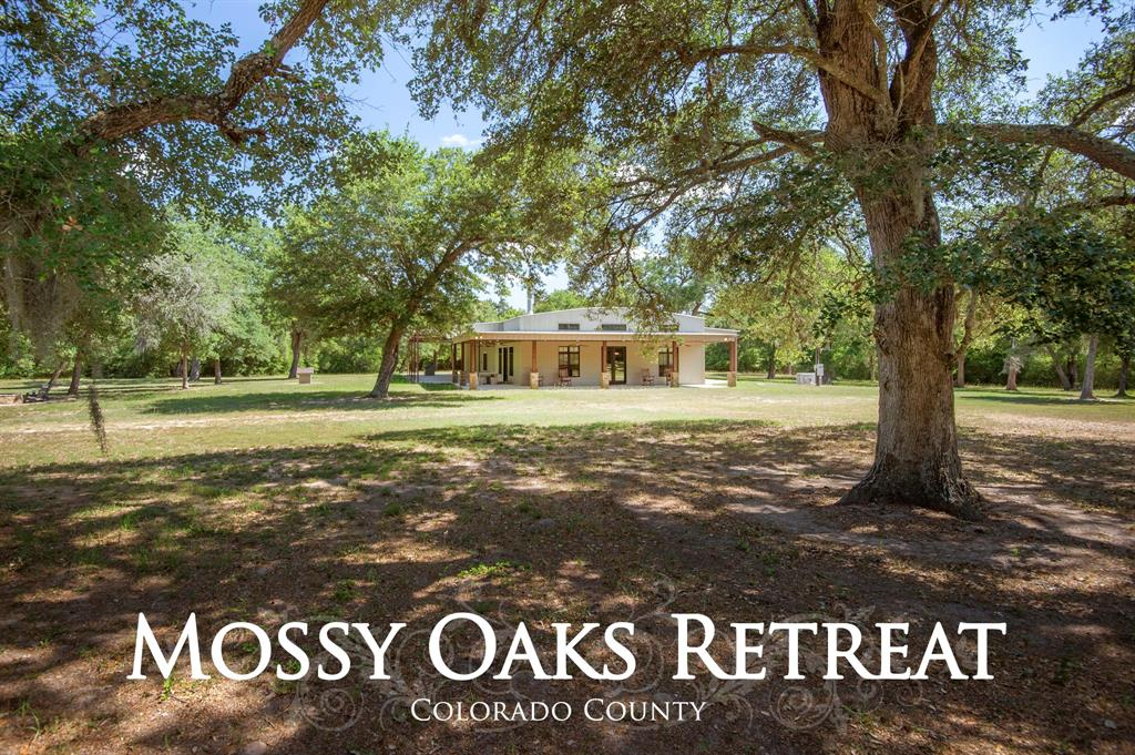 Looking for majestic live oaks highlighting meadows and woods in a peaceful setting, this conveniently located property of 50+/- ac CCAD has it all. Two gated entrances allow use of main residence for personal living and other for the guest house  The artfully designed clearings among wooded areas offer privacy & quiet seclusion for both dwellings. The main house is designed for efficient elegance with a floor plan centered around the spacious main room artfully arranged for kitchen, dining area, living area with fireplace and a reading area. This area accesses the 3600 +/- sq. ft. of covered porches. Add a large master bedroom- bath and a oversized guest bedroom- bath to finish with a large shop attached. The other improvements are a charming 3/2 home with a large front porch overlooking a lovely chain of ponds, live oaks and fishing pier. This grouping has a carport with extra room and a guest house. Lots of possibility for family complex, company retreat or a wonderful country home.