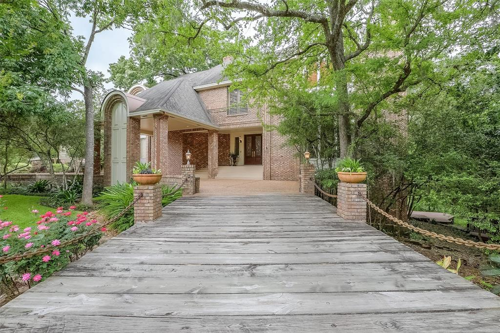 Elegant, One of a kind Home, Over-sized, Wooded Ravine lot.  Interior DID NOT FLOOD. Dramatic Free-Standing Curved Staircase.  20 Ft Ceilings in Living Rm.  Serene Views of Forest & Creek. Wood Burning Fireplace.  Wet-Bar.  Spiral Stairs to Studio & Storage Closet. Over sized Kitchen.  Full Housekeeper suite & access to second floor outside living area.  Master Suite up offers separate His & Her baths and Walk-in Closets.  Fully Equipped Guest Apartment 977SF separate entrance. Attached Carport + Garage.  Three Gas Fireplaces. Five Full Baths & Two half baths.  Plantation Shutters.  Designer Drapery.  10 ft Ceilings thru-out with Crown Molding.  Lots of Updates. Built-ins.Decorator Touches.  House was fully re-plumbed in 2016  All A/C Units were new in 2017.  Ext Painted 2018.  Beautiful Pool.  Re-plaster 2019.  Extensive Decking & Outdoor Shower.  Outdoor Landscape Lighting.  Much More. Private Surrounding Forest.  Nature Walk. Drastic price reduction to account for buyer updates.