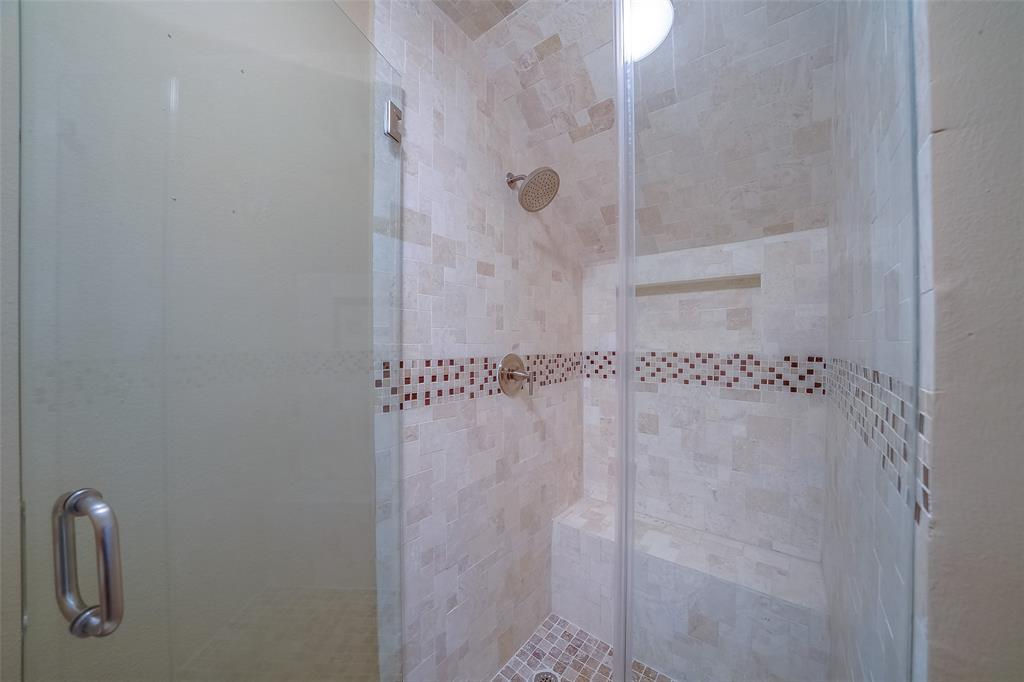Spa-like full bathroom on first floor. Mosaic tiles in the shower with glass door.