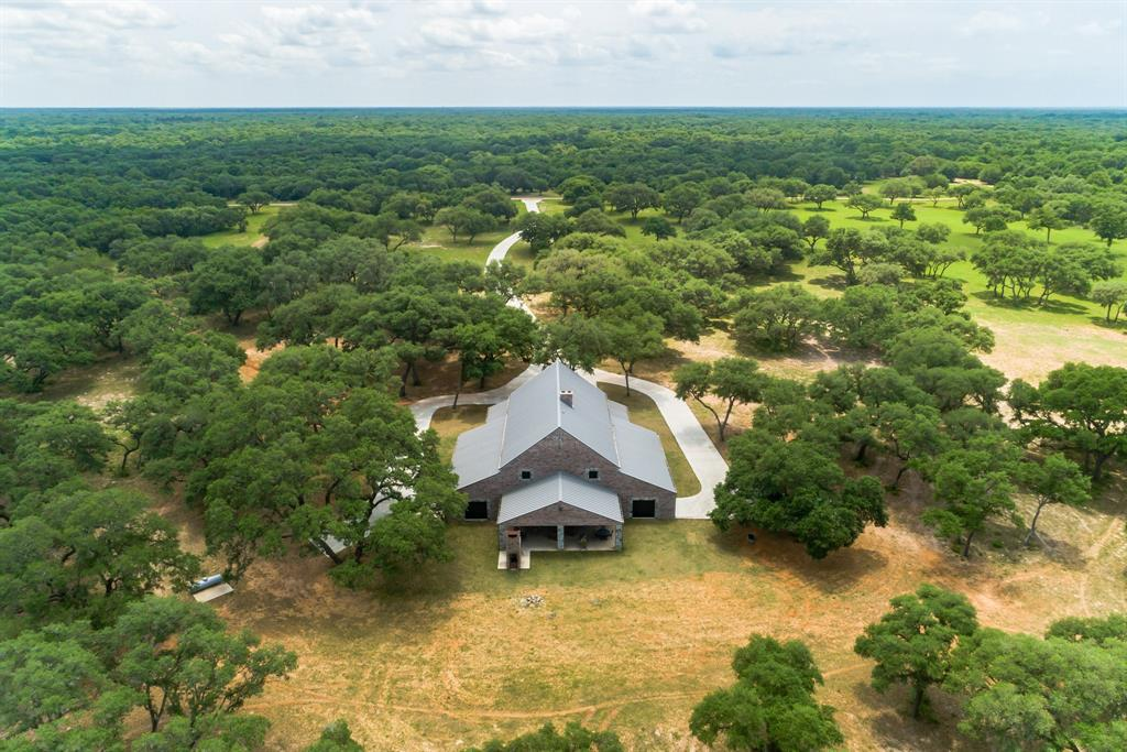PRICED TO SELL!! 90 mins from Houston cross over West Sandy Creek from Colorado County into Lavaca… where Luxury & Country meet. 40-acre high-fenced game ranch w/2 wells, Fallow Deer herd. 12 ft wide paved dr 800 ft to high-end luxury country life. Large parking area with separate concrete drives w/turn around at each garage. Home boast w/beauty, 3 bed, 3 full baths, 3 living areas w/2 gas starter fireplaces, dining room, 2 kitchens, wine cellar, office area, ceilings to 35 ft in family room. Premier granite throughout kitchen, dining, wet bar, rear living area, office area, baths, garages. Open concept, island kitchen w/cook top, French door oven, micro, dishwasher, trash compactor. Ice machine in bar off kitchen along w/wine cellar w/commercial cooling unit capable of storing over 1K bottles of wine, large fireproof safe. Sep living area looking out onto back covered patio w/gas cooktop. Patio w/BBQ pit w/dbl chamber smoker (cook 2 diff temps same time)