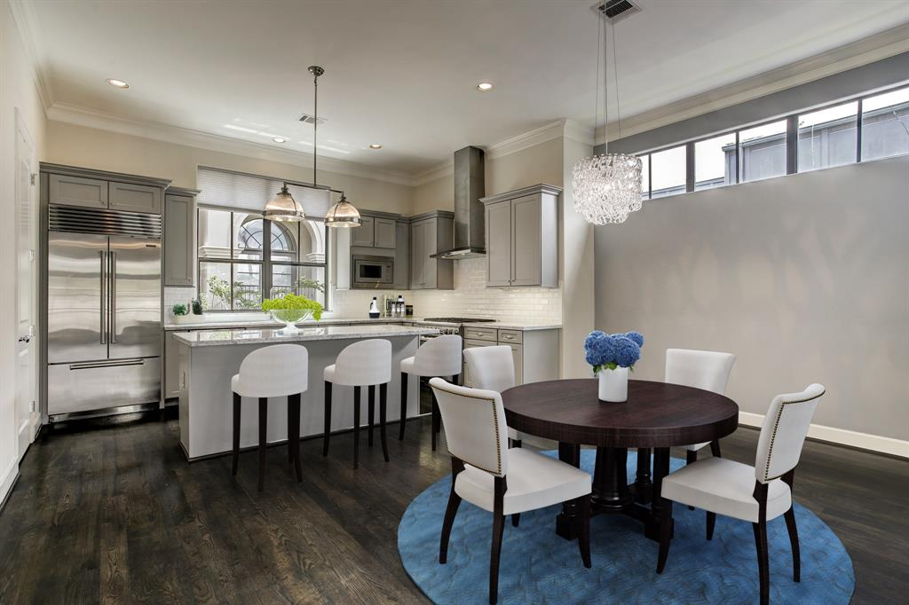 The second floor living level has ample space for a dining set up, and the kitchen includes a custom installed Sub-Zero fridge plus an island with overhang for seating (all virtually staged).