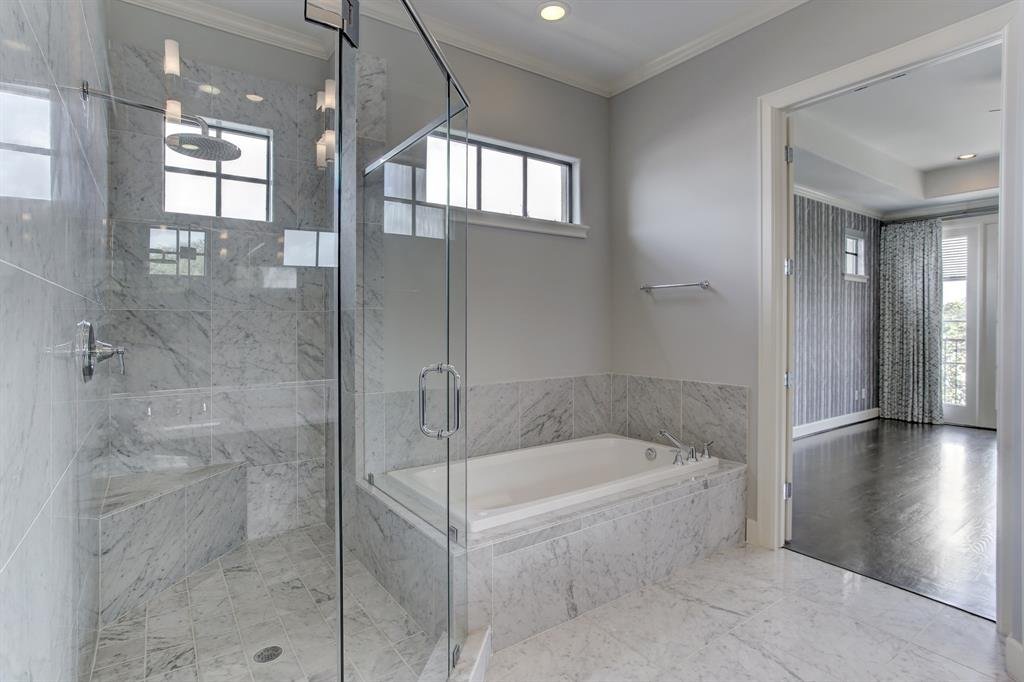 The spa like master bath has a very spacious, frame-less glass shower stall and a jetted tub, along with ...