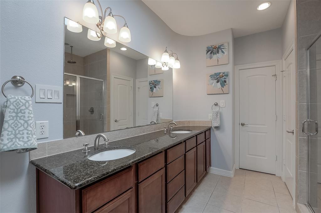 Master bath features dual vanities with granite counter top.
