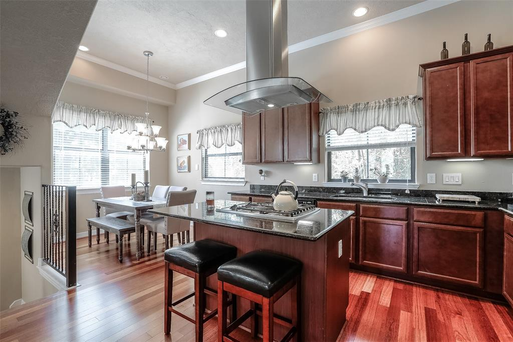 The open floor plan features wood floors, spacious living space and lots of natural light.