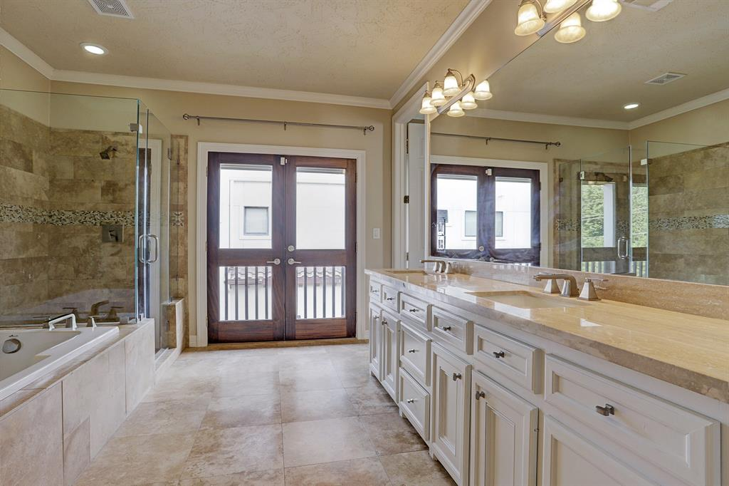 Spacious master bathroom with beautiful tiled floor and walls. Lots of counter space with double sinks.