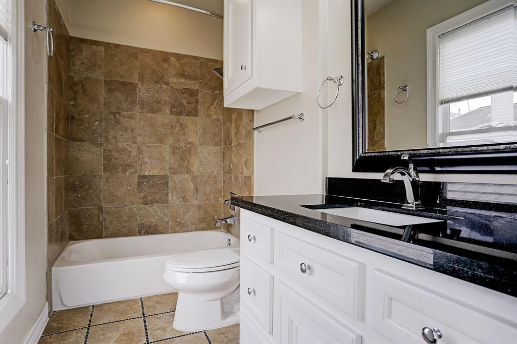 En suite bathroom in third bedroom. Granite counters, tiled shower, and lots of cabinets.