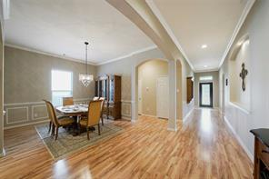 This view showcases how spacious this floor plan is. Laminate wood flooring, crown molding, archways and art niches throughout.