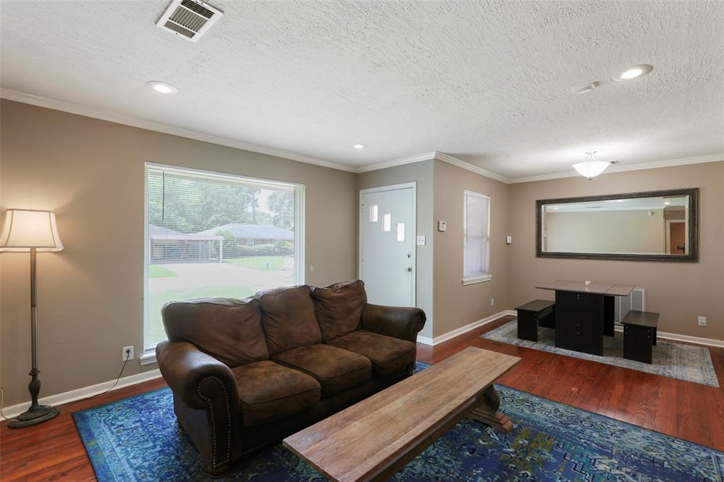 Living room/family room with recessed lighting, large picture window, and gleaming wood floors...