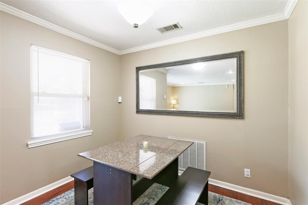 Well-sized dining nook with great lighting and crown molding.