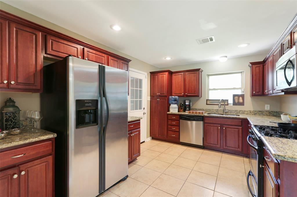 Bright & shiny kitchen with stainless steel appliances and attractive tile floor.