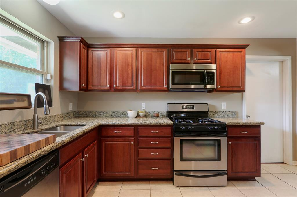 A gas oven/cooktop helps make this a cook's kitchen for sure! Cherry-stained cabinets with plenty of useful storage space.