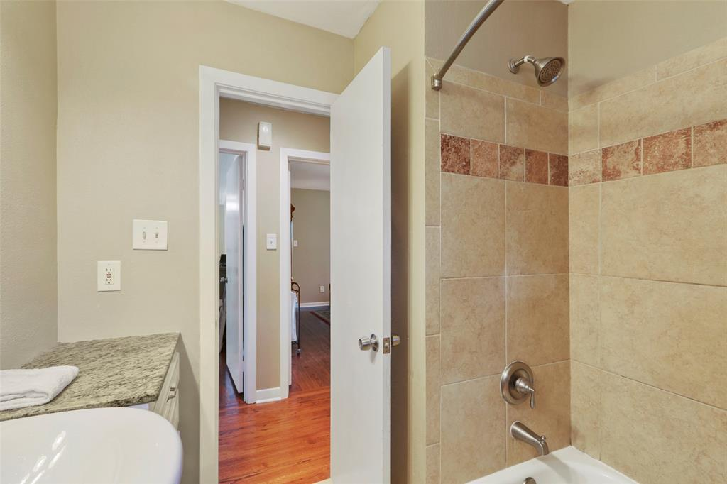 Hall bathroom with bath/shower combination and pretty tile accents.
