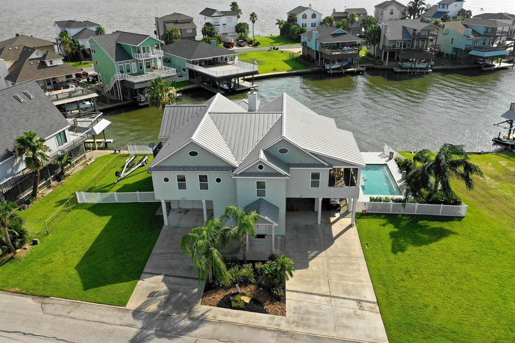 Make this expansive, one story home your full-time Paradise, or a well-appointed retreat.  4-5 Bedrooms, 3.5 baths on a 12,000 sq ft lot, boasting several outdoor living spaces and an elevator. Vaulted ceilings in the living room bring in natural light from the waterfront vistas just outside. Boat house. Large 2nd story deck sits over a large covered patio on the ground floor. That patio serves includes a large bar, kitchen, tv, sitting area, and a half bath. Custom pool features built-in stools that offer views of the canal. Screened porch is served by the pass through windows in the kitchen, creating a year round, outdoor dining experience. Den, which could be a 5th bedroom, offers a quiet, intimate lounging experience, away from the sunshine. Security system in den included. Plenty of storage down stairs, and plenty of green space for the kids/pets. Sprawling layout all on one level. Very functional floor plan.