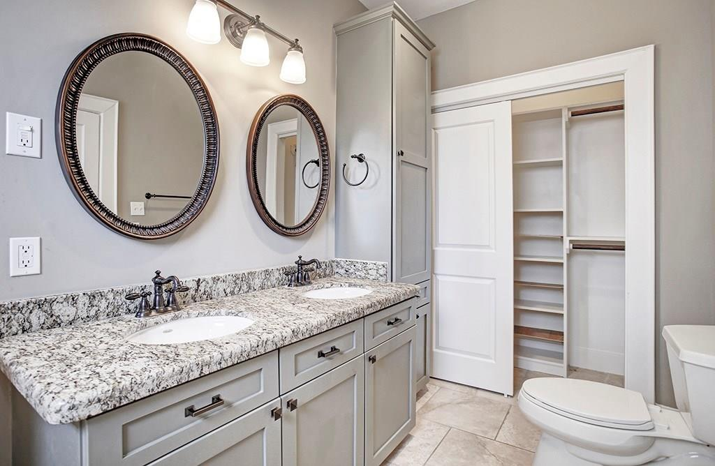 The master bath has a double vanity, cabinet/linen storage and a second closet.