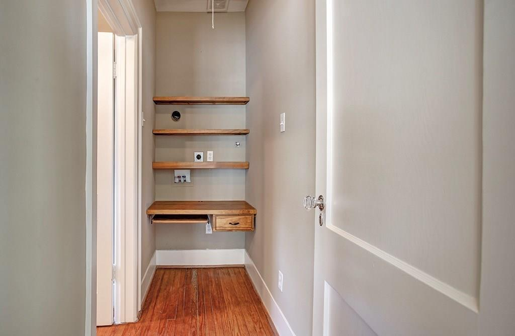 The hall between the living room and second bedroom suite includes a built-in desk area.