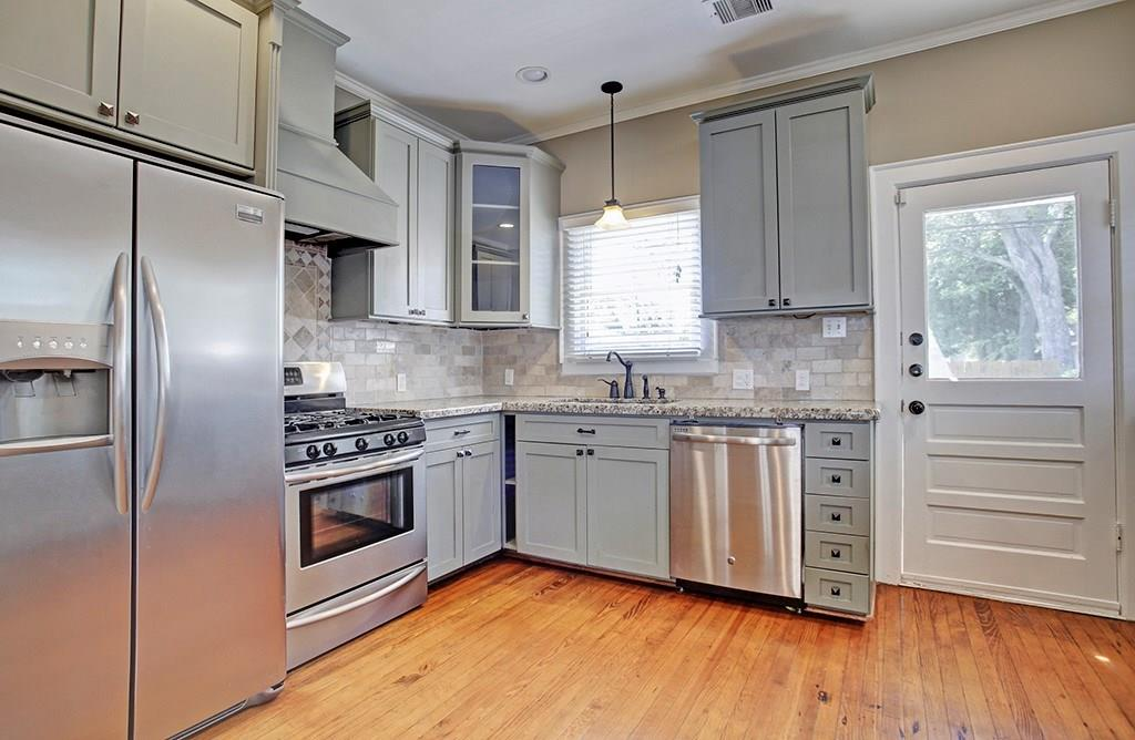 The kitchen has been beautifully updated with stainless appliances, granite counter tops and tile back splash. The door on the right leads to the deck and back yard.