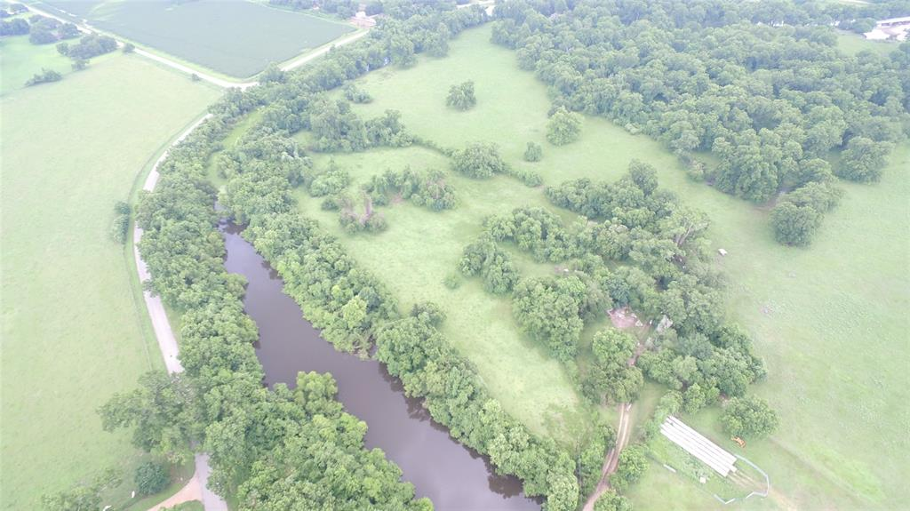 Beautiful wooded tract along Old Caney Road south of Wharton with 3,000' of Caney Creek meandering through property.  Large native pecan trees and large live oaks cover large portion with open and scattered trees covering  the balance.  Fenced, electricity, water well and older 800 sf barn.