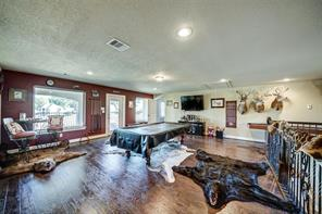 The upstairs game room offers an abundance of natural light, wood floors and an outdoor balcony overlooking the pool and lake.