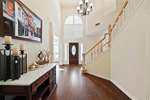Two-story entry is open to the game room above, living room beyond and dining room to the right. The laundry, powder room and garage access is through the hallway to the left.