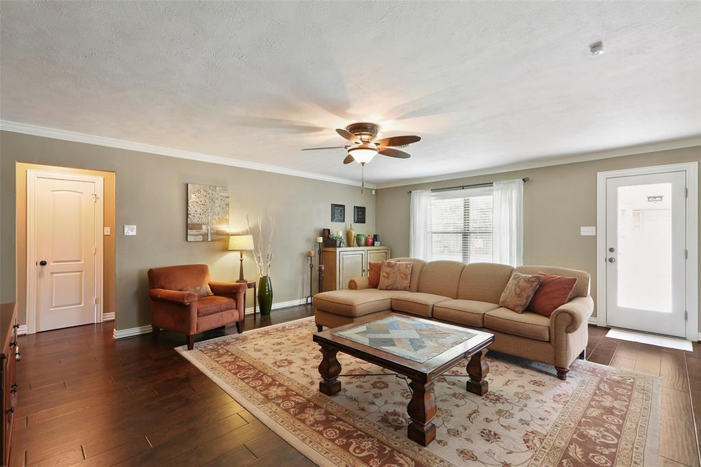 The spacious living room features updated wood floors, crown molding and lots of natural light.