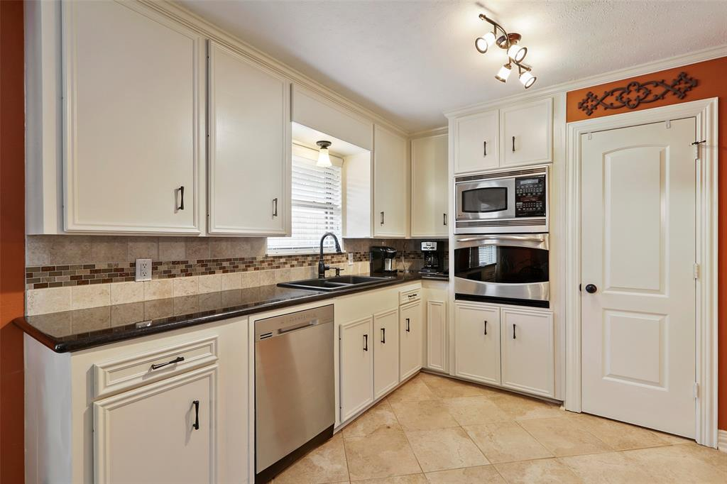 The updated kitchen features granite counter tops, stainless steel appliances and updated tile and back splash.