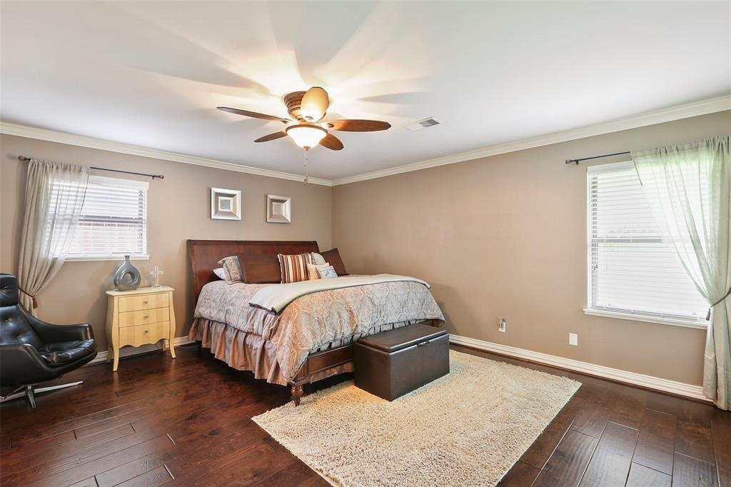 The master bedroom features updated wood floors, great closet space and crown molding.
