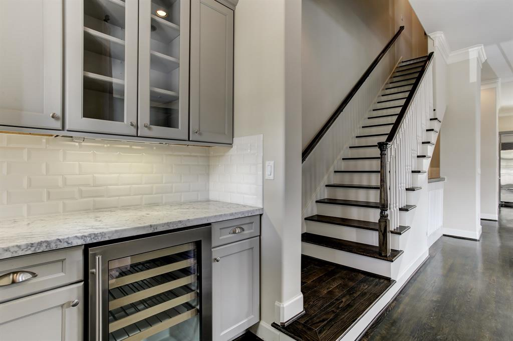 At the front of the living level is a dry bar with additional cabinet storage space and a wine fridge.