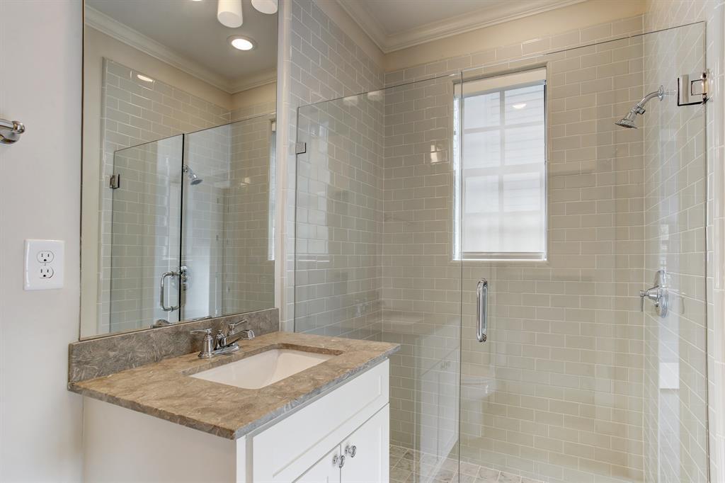 First floor en-suite full bath with frame-less glass shower door.