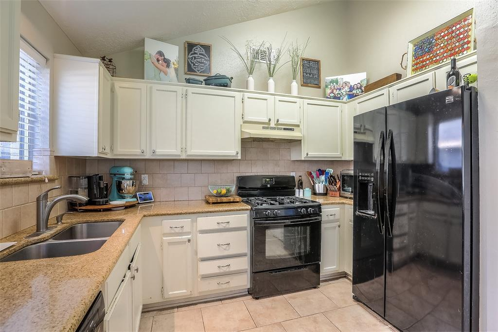 The updated kitchen features granite counter tops, tile flooring and back splash and lots of storage.