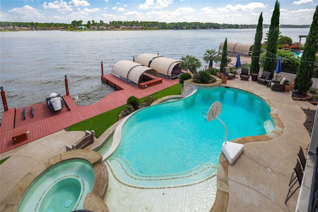Elegant waterfront, custom built home in the gated country club community of Bentwater on Lake Conroe.  This 4 bedroom home has the best of lake life to offer, with gorgeous balcony views, outdoor kitchen, infinity pool & space to entertain both inside & out.  Interior finishes include tray ceilings, crown molding, hardwood & tile flooring, built-in cabinetry, custom art niches, & more.  On the upper level of the home is the kitchen, breakfast area, living, study, & master suite.  The kitchen features granite countertops, professional grade appliances & gorgeous stone surround around the stove & vent. The master suite has a view of the pool and the lake & features an enormous en suite with separate sinks, vanities & ample storage.  The private study includes a custom built-in desk & bookshelf.  While the upstairs is all business, the lower level of the home suggests plenty of time for play, here you will find a game room, media room, wet bar & all the guest bedrooms.  Schedule a tour!