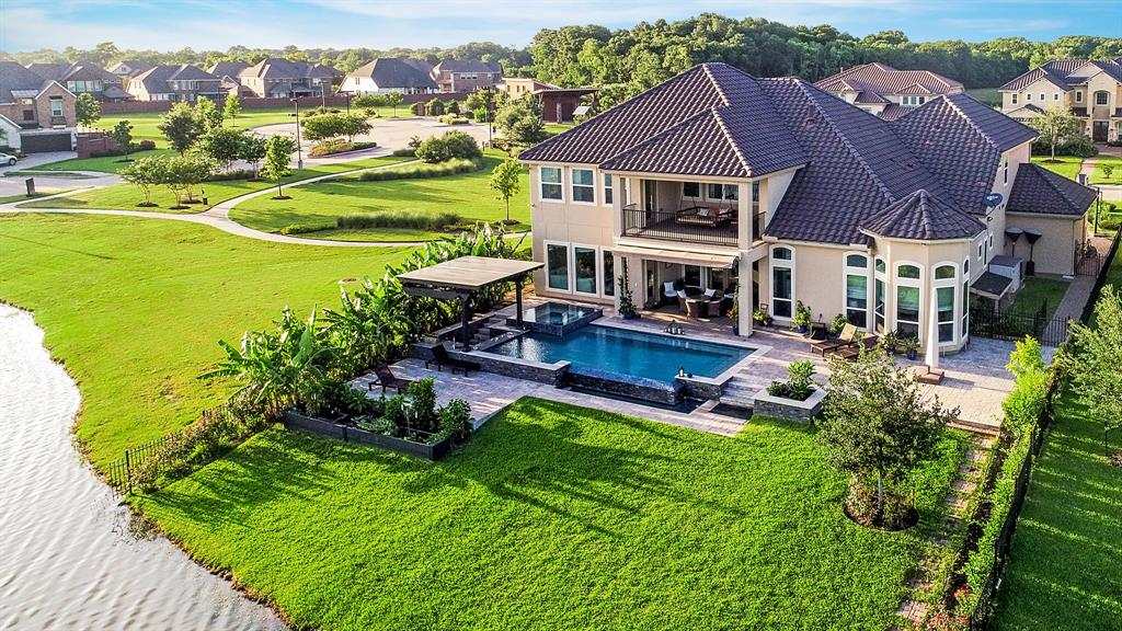 An incredible combination of Resort-Style living in a private tranquil oasis on a cul-de-sac within a gated enclave in the acclaimed Katy ISD. Infinity pool, spa and summer kitchen overlooking the lake with no neighbors on 3 sides. Custom Chef's gourmet Island Kitchen open to two living areas, both with lake views. Provides excellent circulation for entertaining. Downstairs master bedroom with sitting area and custom designed master bath with oversized shower, jetted tub, his/her vanities and closets. Courtyard entry with detached guest house with full bath, media room and game room up in addition to three bedrooms and covered balcony with commanding lake views. Close to the finest schools, restaurants and retail. Many of the furnishings/furniture can convey to buyer at no extra charge with the sale of the house. Contact listing agent for details.