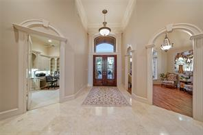 Here is a view of the cut glass double entry door. It is highlighted by additional custom trim work. The formal dining room and office are just off of the entry.