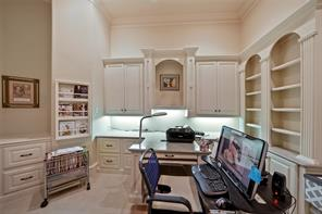The office features beautiful built-ins, file drawers, display shelving, storage and work space. The crisp white cabinetry has a clean and professional look.