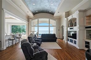 The highlight of the large living room is the barrel ceiling with a custom finish and changes color as the sun comes through the window. Custom millwork for electronics and a grand fireplace create a welcoming space. The view of Lake Conroe is unlike any other!