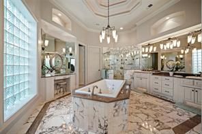 The freshly painted master bath has double vanities, separate make-up area, marble tiled shower and new jetted tub. The neutral backdrop is perfect for any style! Two master closets are just beyond.