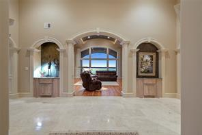 The grand entry has extensive trim and molding throughout, travertine flooring and custom art niches.