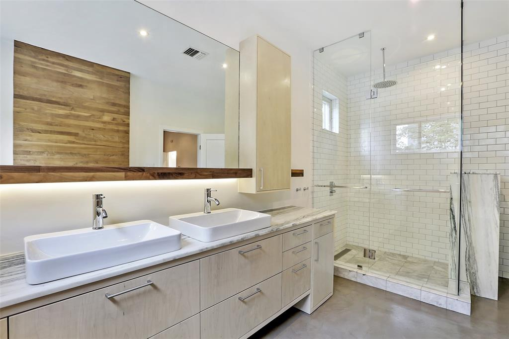 This stylish master en suite includes double vanities in the master bathroom, a separate shower with subway tiled surround, marble counter-tops, low flow duel flush toilets, rain head shower head and an accent wall with walnut paneling.