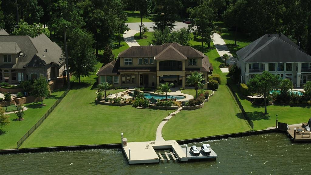 Located on 1.5 lots, this grand waterfront home boasts 139' of waterfront living with majestic open water views of Lake Conroe. Relax in the 20,000gal Pool & Spa, watch the kids from a massive covered patio, & entertain with a full outdoor kitchen that includes a Big Green Egg. Inside, the family room features majestic lake views, a stone fireplace, built-ins & beam ceiling. A gourmet kitchen opens to the family room & boasts luxury granite counters, large island, & Thermador Appliances: double ovens, 6-burner cooktop, wine fridge, separate icemaker & built-in refrigerator. 2 BEDROOMS FIRST FLOOR! ALL BEDROOMS ARE EN'SUITE & 3 OFFER INCREDIBLE LAKE VIEWS! Master suite offers wainscot beam ceiling, a spa-like bath with big dual-head shower, two walk-ins, two vanities & whirlpool tub & more fantastic lake views.  Gameroom and screened balcony overlook the pool and Lake Conroe.  Awesome media room! Big dock with a boat lift, & two Jet Ski lifts.  ...THE LAKEFRONT HOME YOU HAVE DREAMED OF!