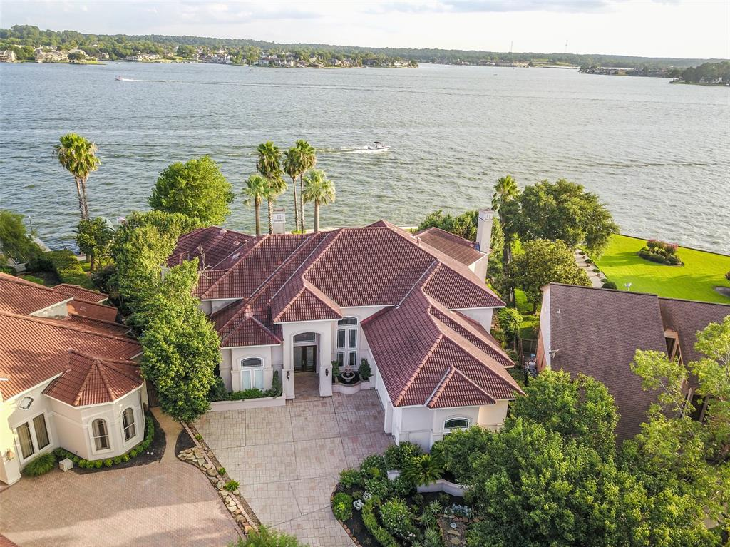 Take in the very best views of Lake Conroe from almost every area of this RARE waterfront estate. Perfectly situated on one of the most desirable lots on the Lake w/230ft of waterfront w/fresh bulkhead, boardwalk, boat slip w/lift, jet ski lift, putting green, outdoor kitchen w/stacked FP, fire pit, pool/spa + decking covered/uncovered, miles of Southern Lake views that will make relaxing/entertaining an unforgettable experience. From the first step inside the quality & panoramic views will grab your attention. The house was designed for Lake Living from the living room w/a 2 story wall of windows that lead to a pool front lanai to the island kitchen w/generous counter space, bar w/ice,fridge,chiller, wine area then to the den w/large picture windows w/unobstructed views & all lead to covered/uncovered patios. Master suite boasts sitting area + FP, wall-2-wall views, spa-like bath w/2 walk-in closets. Upstairs: Game room w/wet bar + lounge, balcony/patio, media room + 3 beds/3.5 baths.