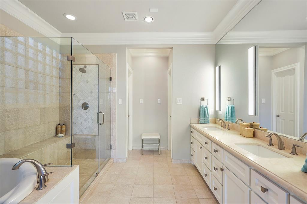 The massive shower features a modern glass enclosure with upgraded tile accent.