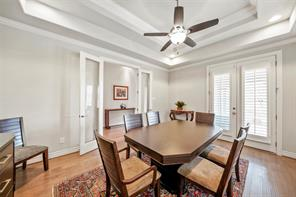 Another view of the formal dining room showing the double glass doors on the left which lead to the entry hallway, and double doors on the right with the plantation shutters that lead to the covered front porch. Note raised ceiling with double crown and upgraded ceiling fan and light.
