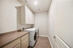 Utility room has upper cabinets as well as a folding table with lower cabinets and is located on the main level of the home.