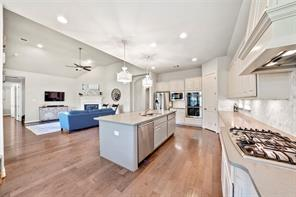 Very open floor-plan is great for entertaining. Large center island with quartz counters; SS appliances with double ovens and gas cook-top. Wood flooring was installed here and throughout most of the bottom floor of the home.