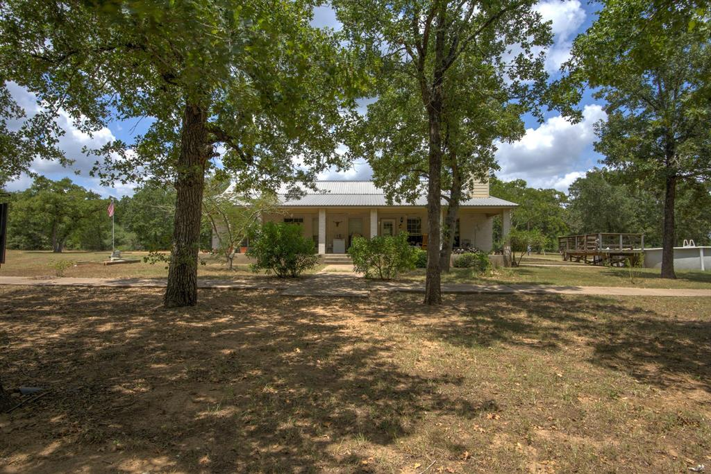 Park like setting in Bastrop county!  Custom home w/Austin Stone, open floor plan, lots of storage & large covered porch overlooking beautiful pond! Relax in your private retreat, enjoy wildlife & rec trails thru woods & pastures.  Beautiful corner fireplace built w/petrified stack rock found on property!  Solar attic fan & Mylar help keep house cool & elec bills low. Outbuildings include barn, cabin/party building with 1 bedroom w/half bath + storage rm & patio for addl guest quarters.